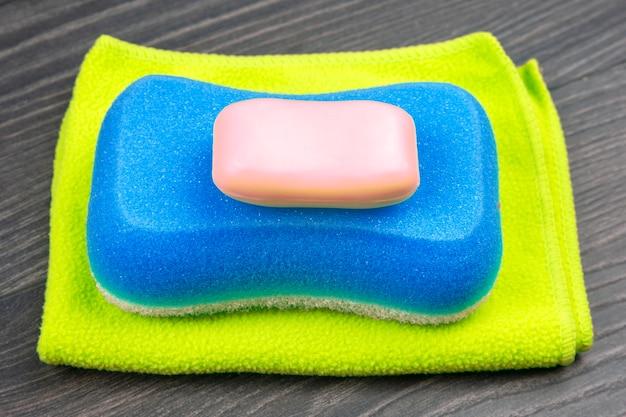 Губка для мытья в ванной, мыло и полотенце на деревянном