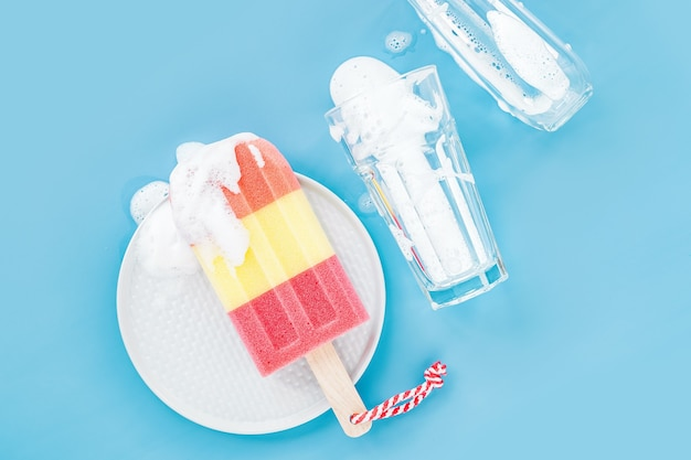 Sponge in the form of ice cream and glass on soapy foam background. washing dishes concept. flat lay, top view.