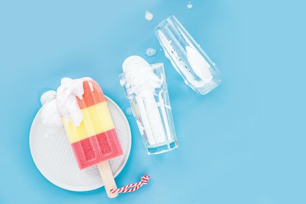 비누 거품 배경에 아이스크림과 유리 형태의 스폰지. 설거지 개념입니다. 평면 위치, 상위 뷰.