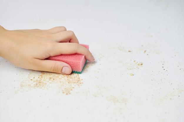 Губка в руке женщины удаляет грязь, панировочные сухари и остатки еды. уборка кухонного стола. работа по дому