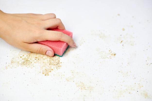 女性の手のスポンジは、汚れ、パン粉、残り物を取り除きます