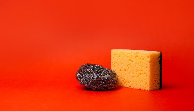 Sponge and metal mesh for cleaning on a red background