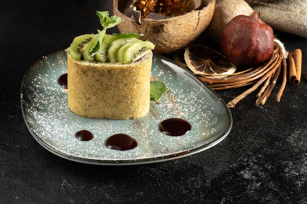 Sponge roll with kiwi and chia seeds. classic sweet dessert with fruit and berry sauce. biscuit