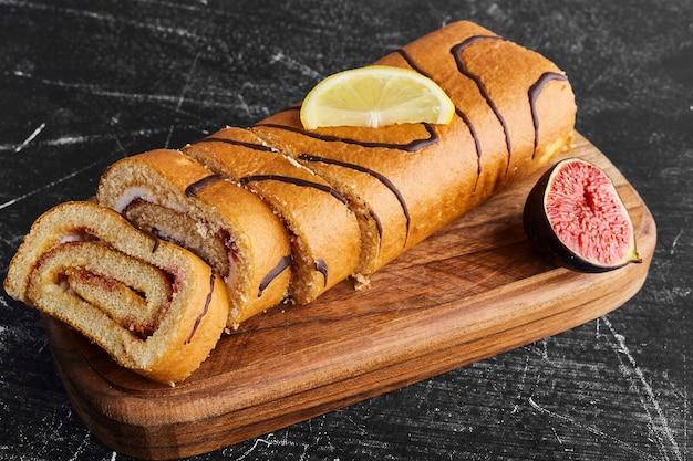 Pan di spagna con ripieno di cioccolato su una tavola di legno.