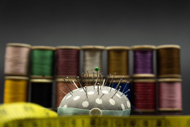 Sponge of sewing needles and spools of thread on the back