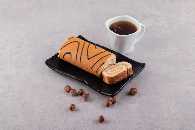 헤이즐넛과 테이블에 차 한잔 스폰지 스위스 롤 케이크.