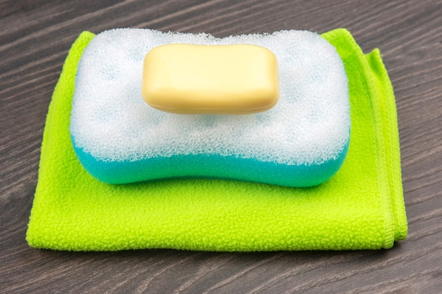 Sponge for washing in the bathroom, soap and towel on wooden background