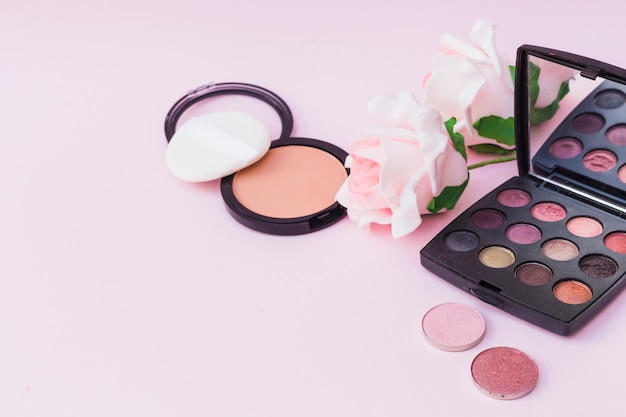 Sponge with blusher; pink rose and eyeshadow palette on colored background