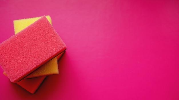 Губки - крупный план. концепция бытовой уборки. красочные оранжевые розовые желтые губки на розовом фоне, мягкий фокус, копия текста.