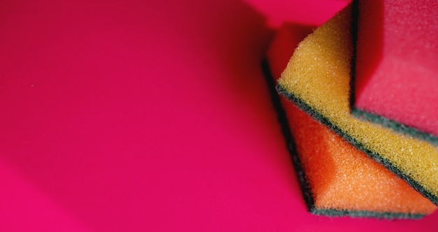 Sponges - close-up. household cleaning concept. colorful orange pink yellow sponges on pink background, soft focus, copy text.