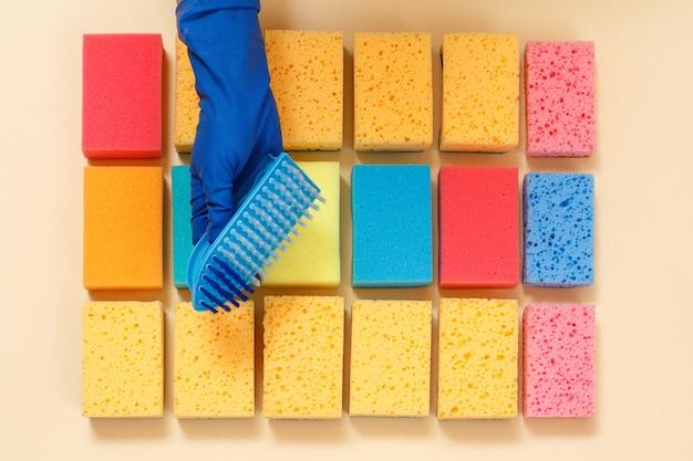 Губки разного цвета и рука в резиновой перчатке с пластиковой кисточкой на бежевой поверхности.