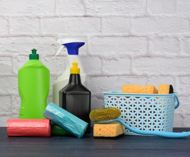 Sponges, plastic brushes and bottles of detergents on a blue wooden table. household cleaning items on white brick wall surface