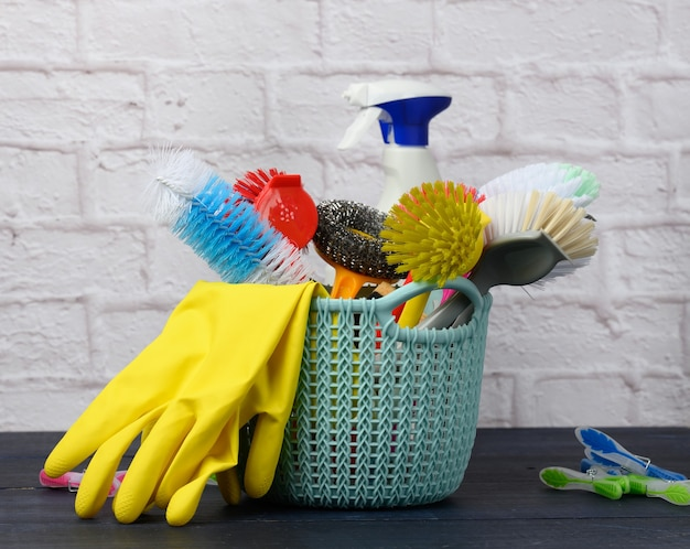 Sponges, plastic brushes and bottles of detergents on a blue wooden table