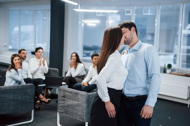 2人の従業員間の自発的な素敵なキスは他のオフィスワーカーに衝撃を与えました
