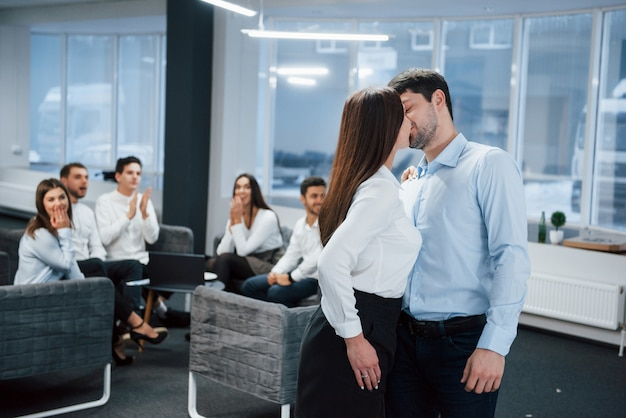 Spontaneous lovely kiss between two employees shocked other office workers