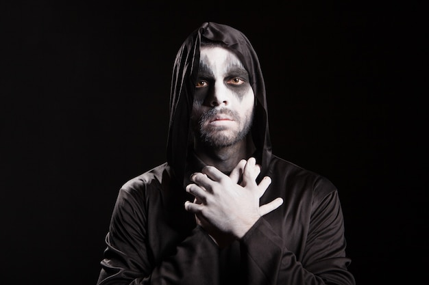 フード付きの黒い背景の上の不気味な死の天使。ハロウィーンの衣装。