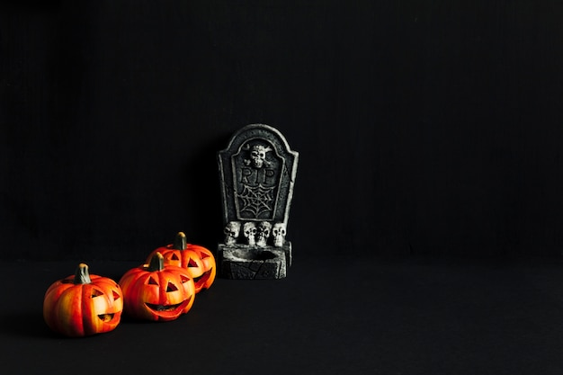Spooky composition for halloween with tombstone and pumpkins