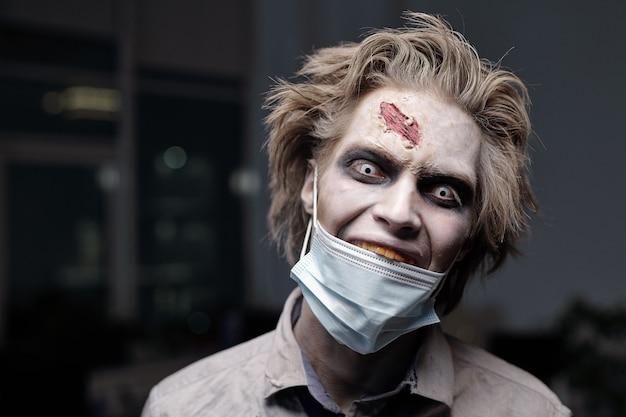 어두운 사무실 환경에 서 있는 동안 우울한 미소로 당신을 바라보는 얼굴에 보호 마스크를 쓴 으스스한 죽은 사업가