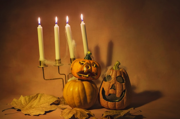 Spooky evening hallowen pumpkins with candle candlestick on orange background