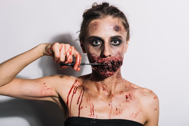 Spooky female cutting stitched mouth with scissors