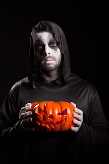 Spooky grim reaper holding a pumpkin over black background, halloween outfit.
