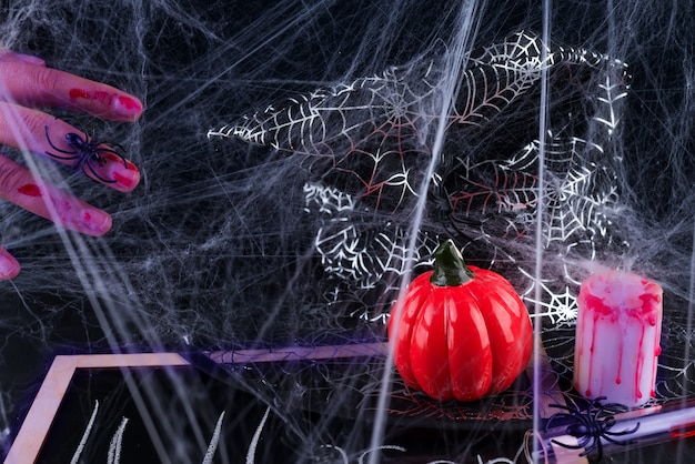 Spooky halloween background with bloody hands, pumpkins, cobwebs, spiders
