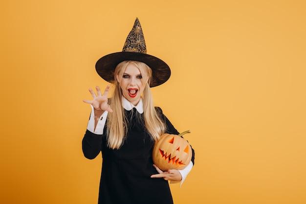 Пугающая девушка хэллоуина с тыквой в руках на оранжевом стенном фоне. фото высокого качества