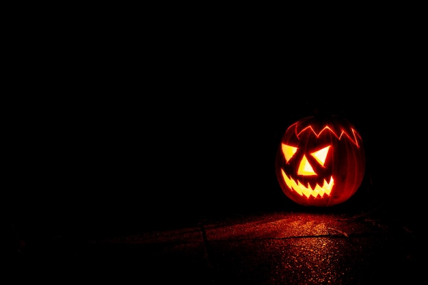 暗闇の中で夜の不気味なハロウィーンのカボチャのランタン