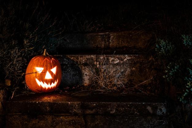 夜の庭のコンクリートの階段に不気味なハロウィーンのカボチャのランタン