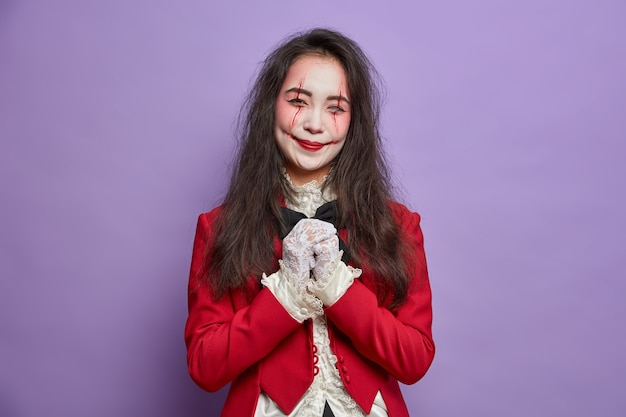 Spooky happy woman has image of zombie keeps hands together wears ghost makeup poses for halloween poster isolated on purple wall