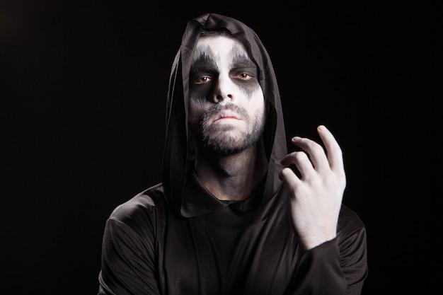 不気味な男は、黒い背景の上に死神のようにドレスアップしました。ハロウィーンの謎。