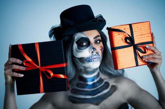 プレゼントを保持しているハロウィーンのゴシックメイクの女性の不気味な肖像画