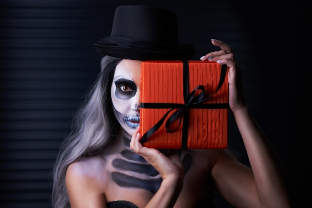 Spooky portrait of woman in halloween gothic makeup holding present