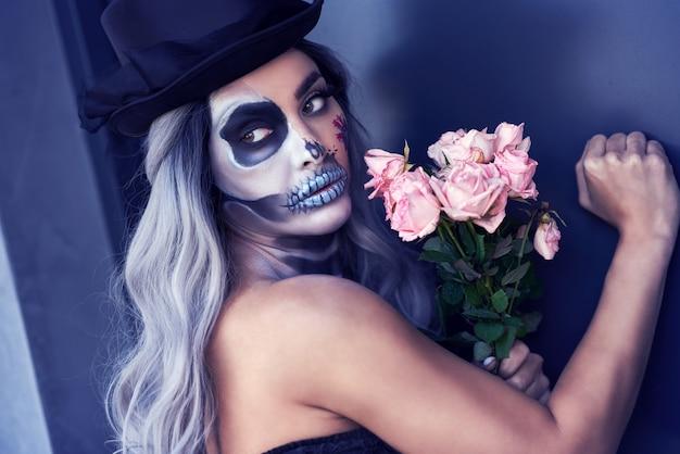 Spooky portrait of woman in halloween gothic makeup knocking on door