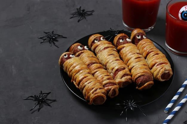 어두운 접시에 할로윈 파티를 위한 으스스한 소시지 미라와 토마토 주스. 아이들을 위한 재미있는 음식 아이디어. 텍스트를 위한 공간입니다.