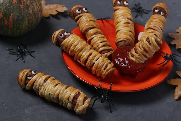 할로윈 파티를위한 케첩과 반죽에있는 무시 무시한 소시지 미라가 회색 테이블에 제공됩니다.