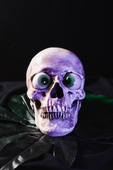 Spooky skull with fancy eyeballs illuminated by purple light