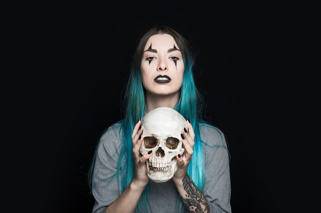 Spooky woman holding human skull
