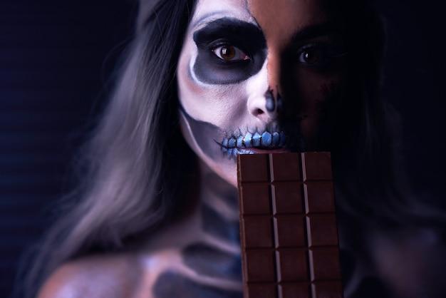 チョコレートのバーを保持しているハロウィーンのゴシックメイクで不気味な女性