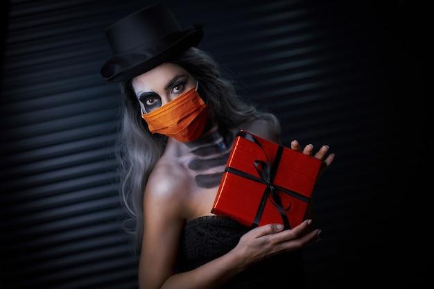 Жуткая женщина в готическом макияже на хэллоуин в маске из-за ограничений covid-19