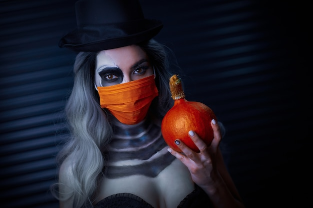 Covid-19の制限のためにフェイスマスクを身に着けているハロウィーンのゴシックメイクの不気味な女性 Premium写真