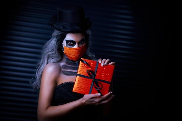 Covid-19の制限のためにフェイスマスクを身に着けているハロウィーンのゴシックメイクの不気味な女性