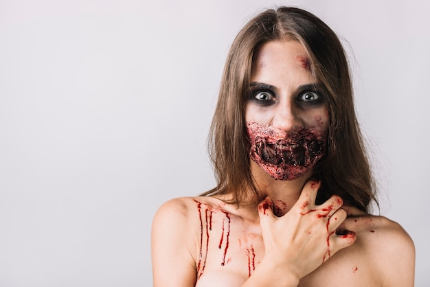 Spooky woman with damaged face scratching neck