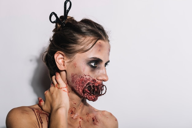 Spooky woman with damaged face touching neck