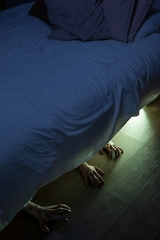 Spooky zombie hands under the bed