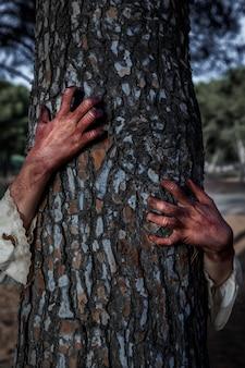 Mani spettrali di zombie su un albero
