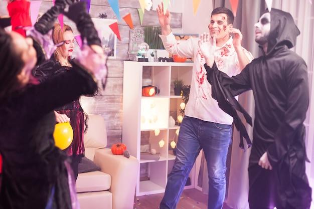 人々のグループとのハロウィーンパーティーで踊りながら微笑んでいる不気味なゾンビ。