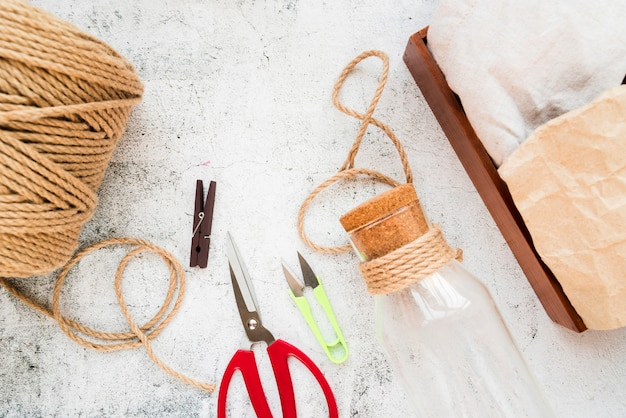 Spool of jute string; clothespin; scissor and glass bottle with cork over textured background