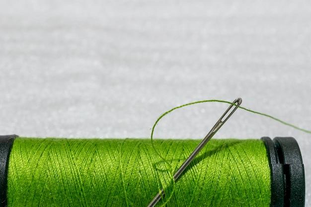 テキスト用のスペースがある、針付きの緑色の糸のスプール。