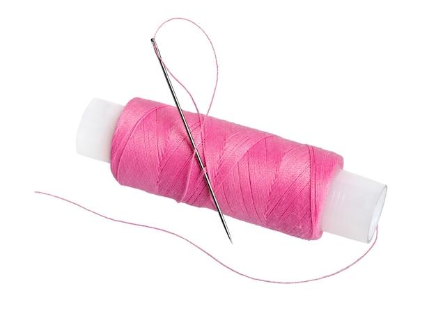白い表面で隔離された針と糸のスプール
